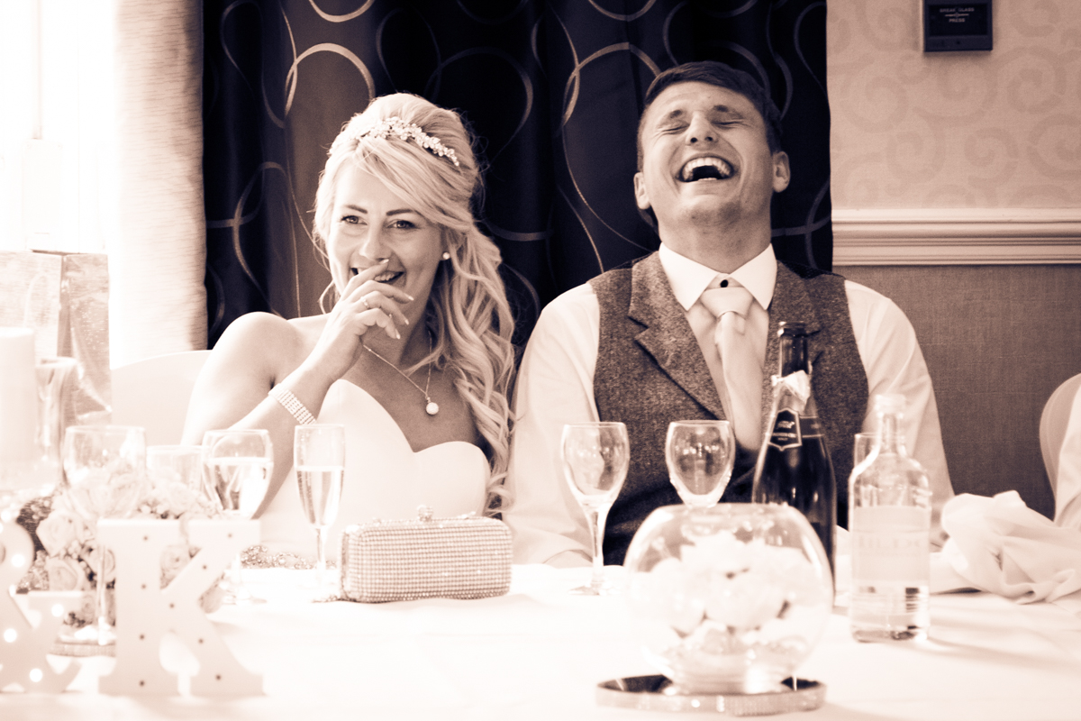 The bride and groom sat laughing during the best mans speech at their Puckrup Hall wedding.