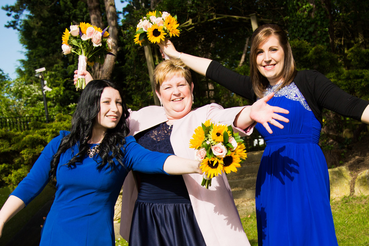 Bride stood with her bridesmaids doing jazz hands.