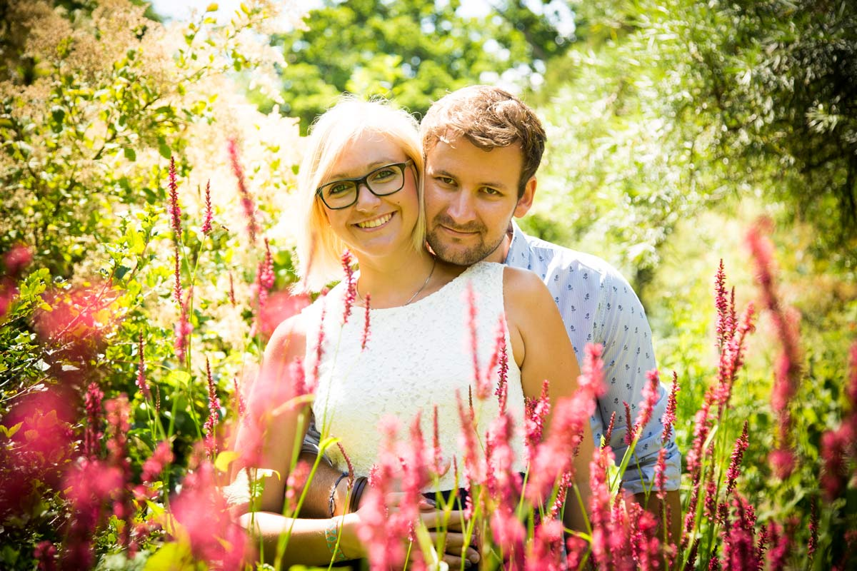 A couple stood behind some pink flowers in a garden, during an engagement shoot.
