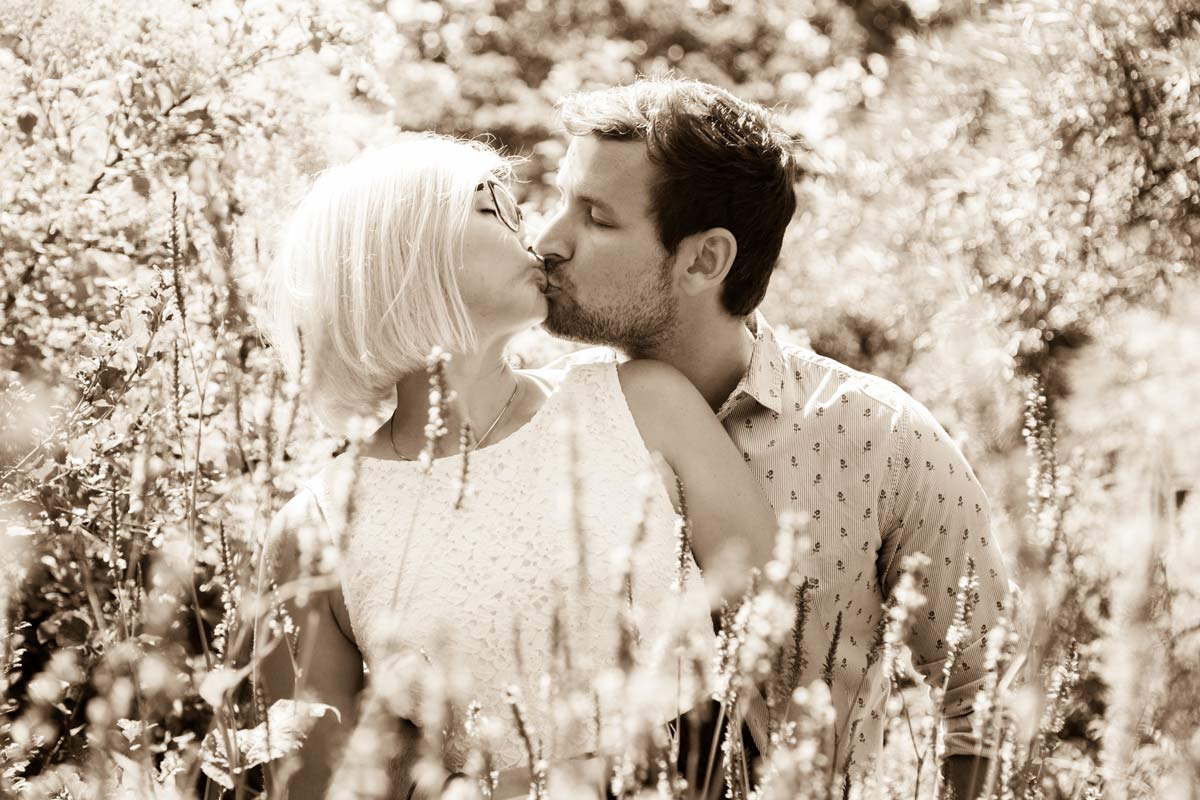 A couple stood behind some flowers kissing, during their engagement shoot.