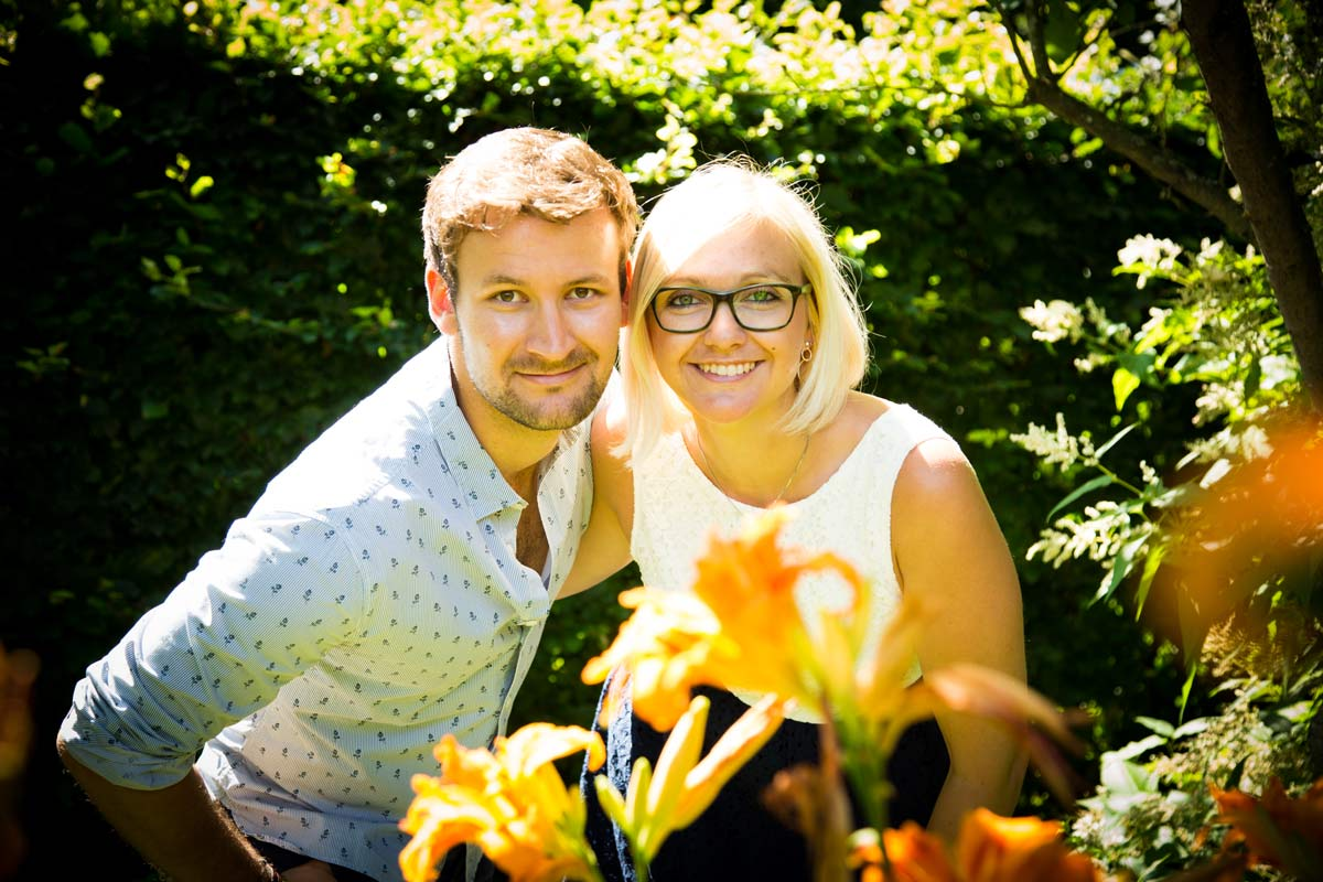 A couple posing in front of some flowers in a garden.