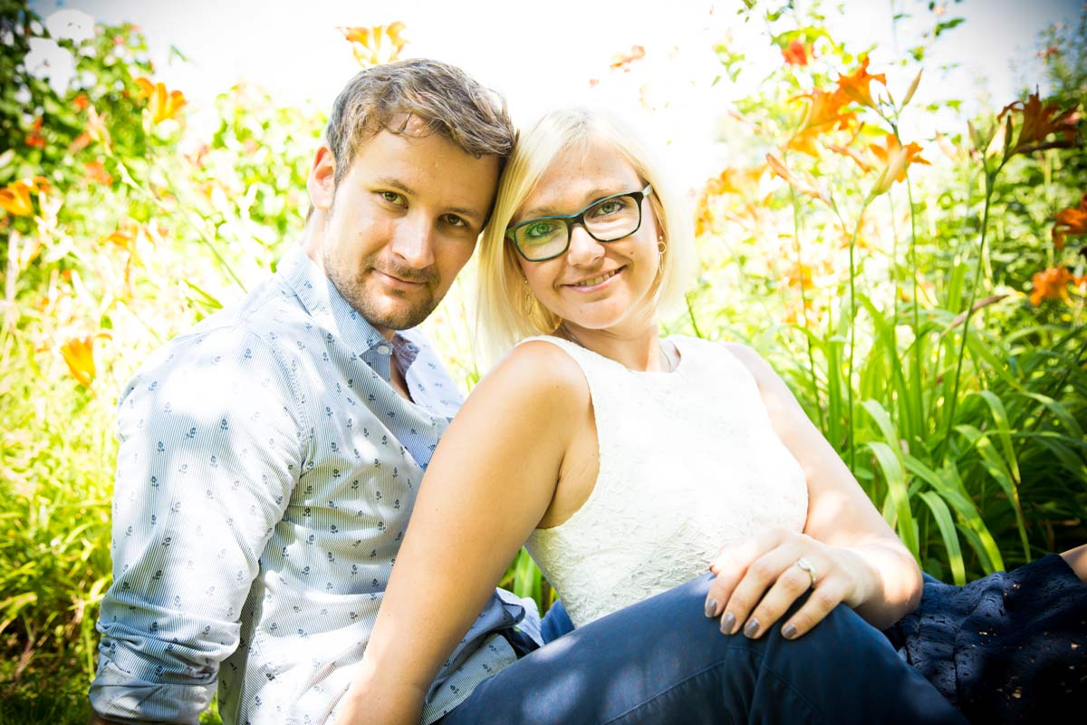 A couple sat in a garden touching heads, during their engagement shoot.