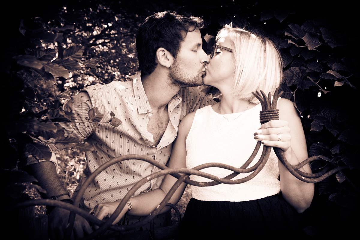 A couple kissing behind some twisted iron, during an engagement shoot.