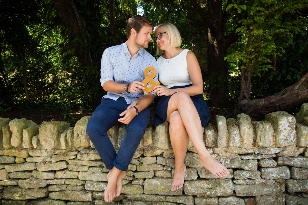A couple sat on a Cotswold stone wall, holding an '&' sign during their engagement shoot.