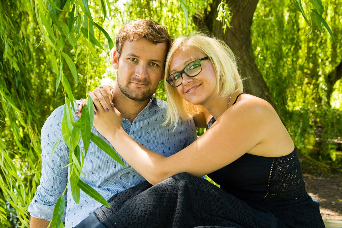 An engaged couple sat under a tree hugging, during their Worcestershire Engagement shoot.