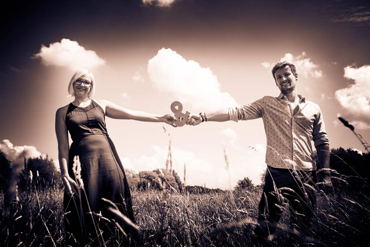 A couple stood in a field, holding up an & sign, against the sky.