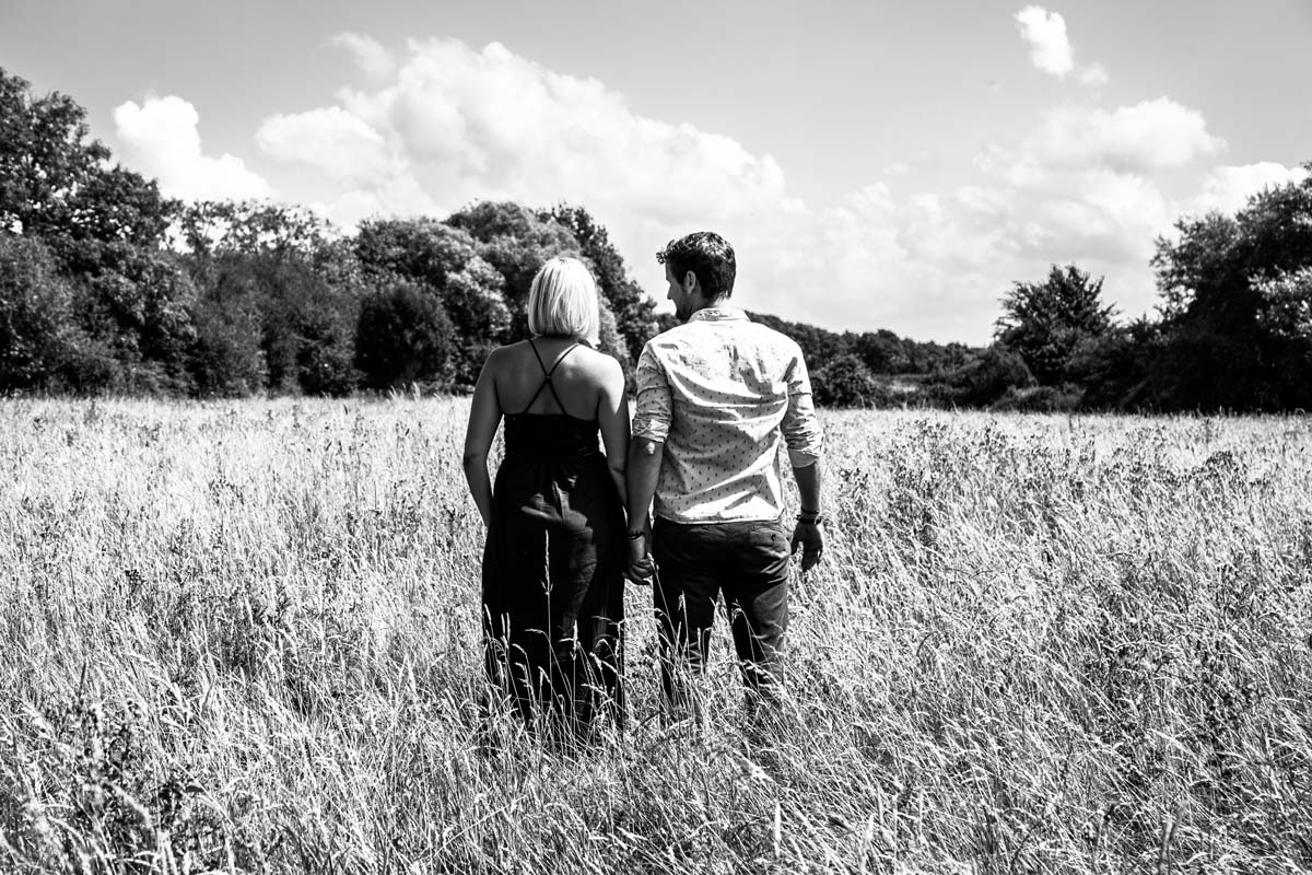 The back of a couple as they walk away across a field, during an engagement shoot.