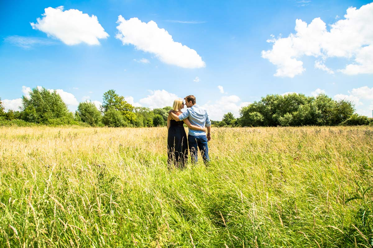 A couple stood in a field on a sunny day with an arm around each other.