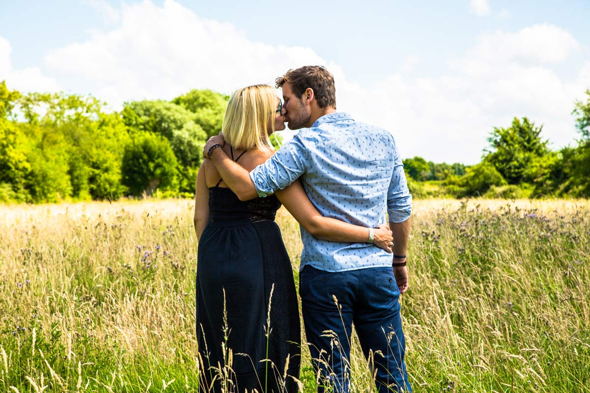 A couple stood in a field kissing, with an arm around each other during an engagement photo shoot.