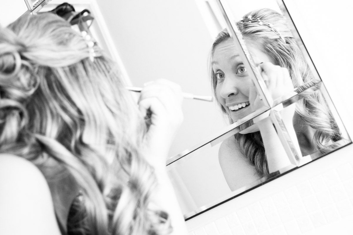 Brides mirror reflection as she does her wedding makeup.