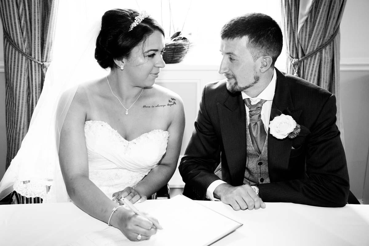 Bride signing the wedding register in Cheltenham.