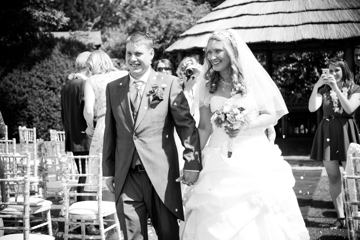 Bride and groom walking down the aisle at their garden wedding.