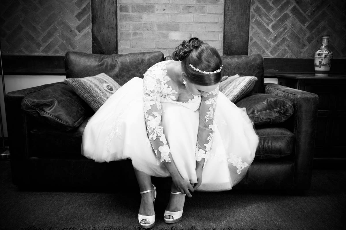Bride putting her wedding shoes on in Berrow, Worcestershire.