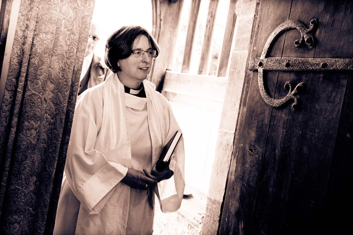 Female priest entering the church at St Faith's, Berrow, Worcestershire.