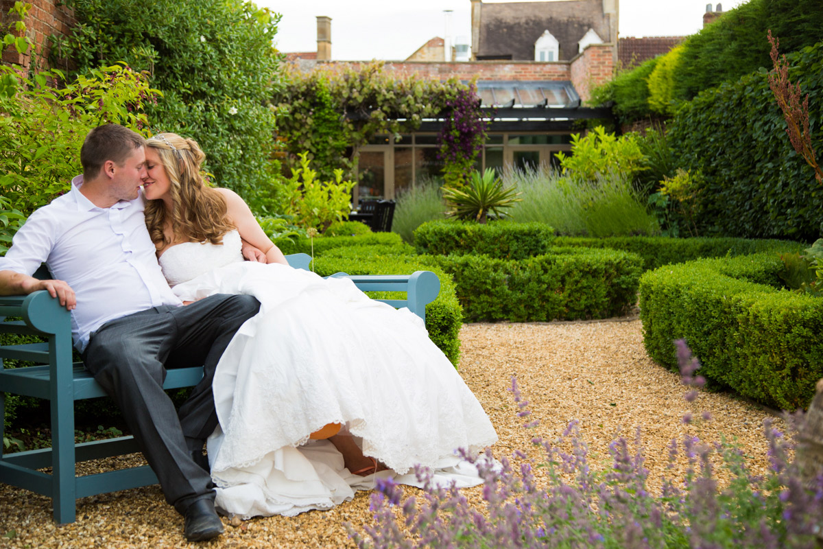 Bride and groom kissing on a bench in Moreton-in-Marsh.
