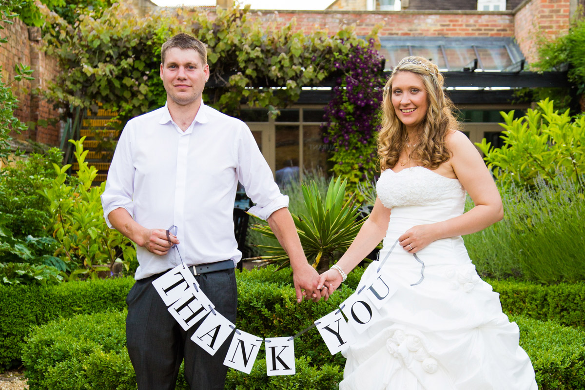 Bride and groom holding thank you sign in the Manor House Hotel garden.