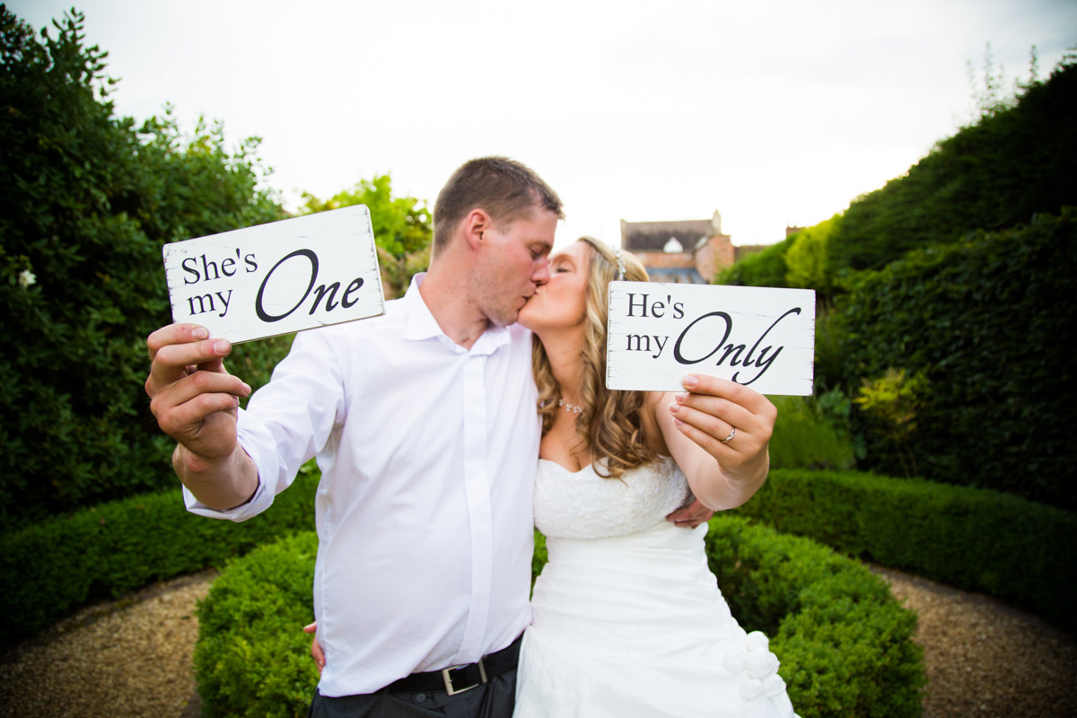 Bride and groom holding she's my one, he's my only wedding signs.