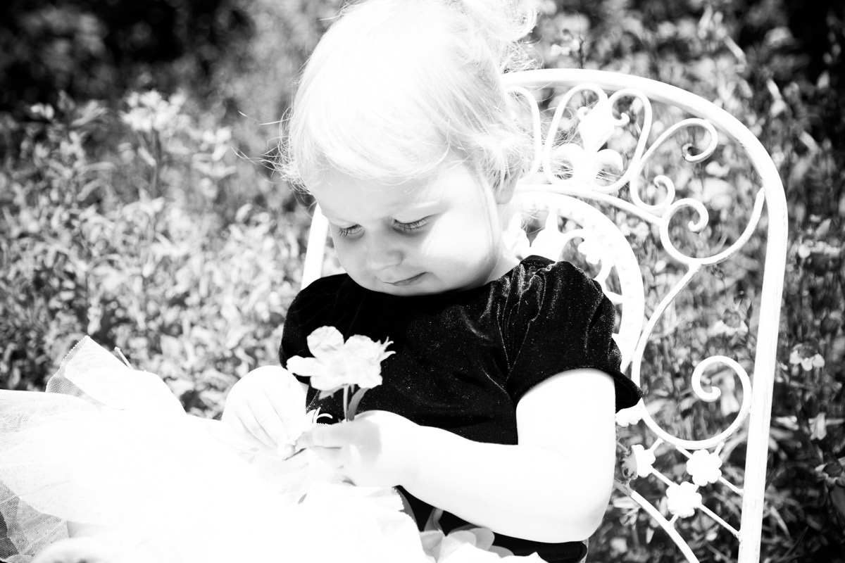 A little girl sat on a metal chair, playing with a flower during photo shoot in Gloucestershire.