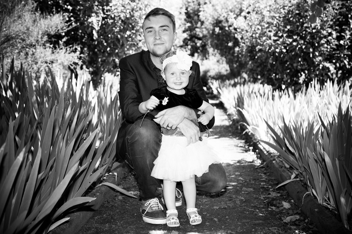 A young man holding a little girl in a cottage garden.