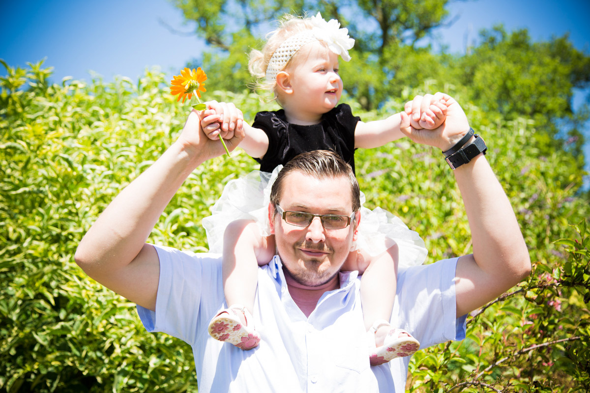 A dad carrying his little girl on his shoulders in a cottage garden.