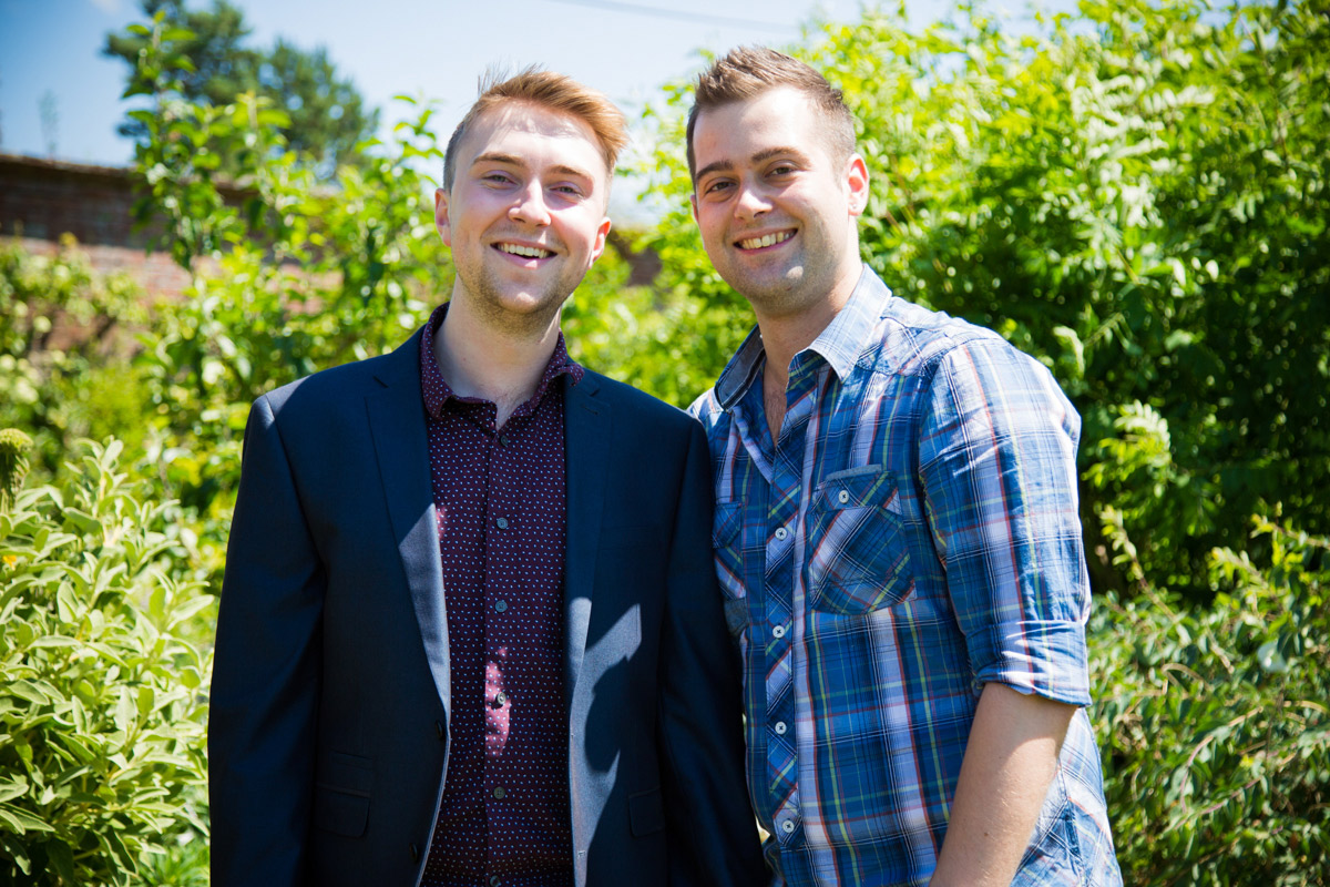 Two young men stood smiling in a cottage garden.