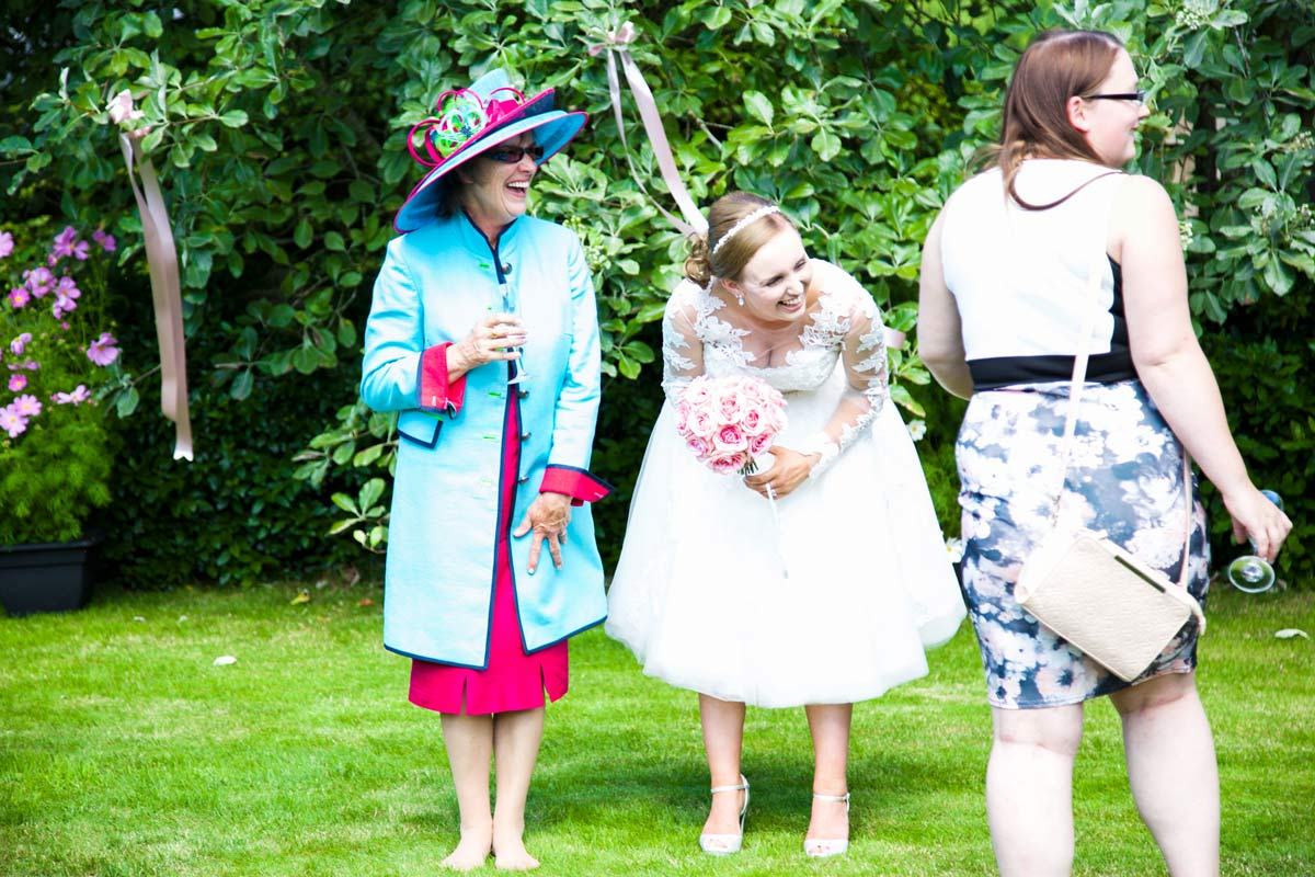 Bride and her mother stood laughing in a country garden.