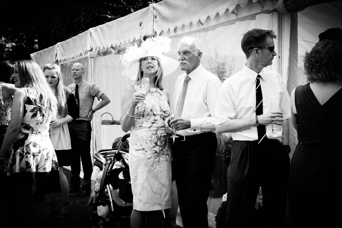 Wedding guests stood outside a marquee.