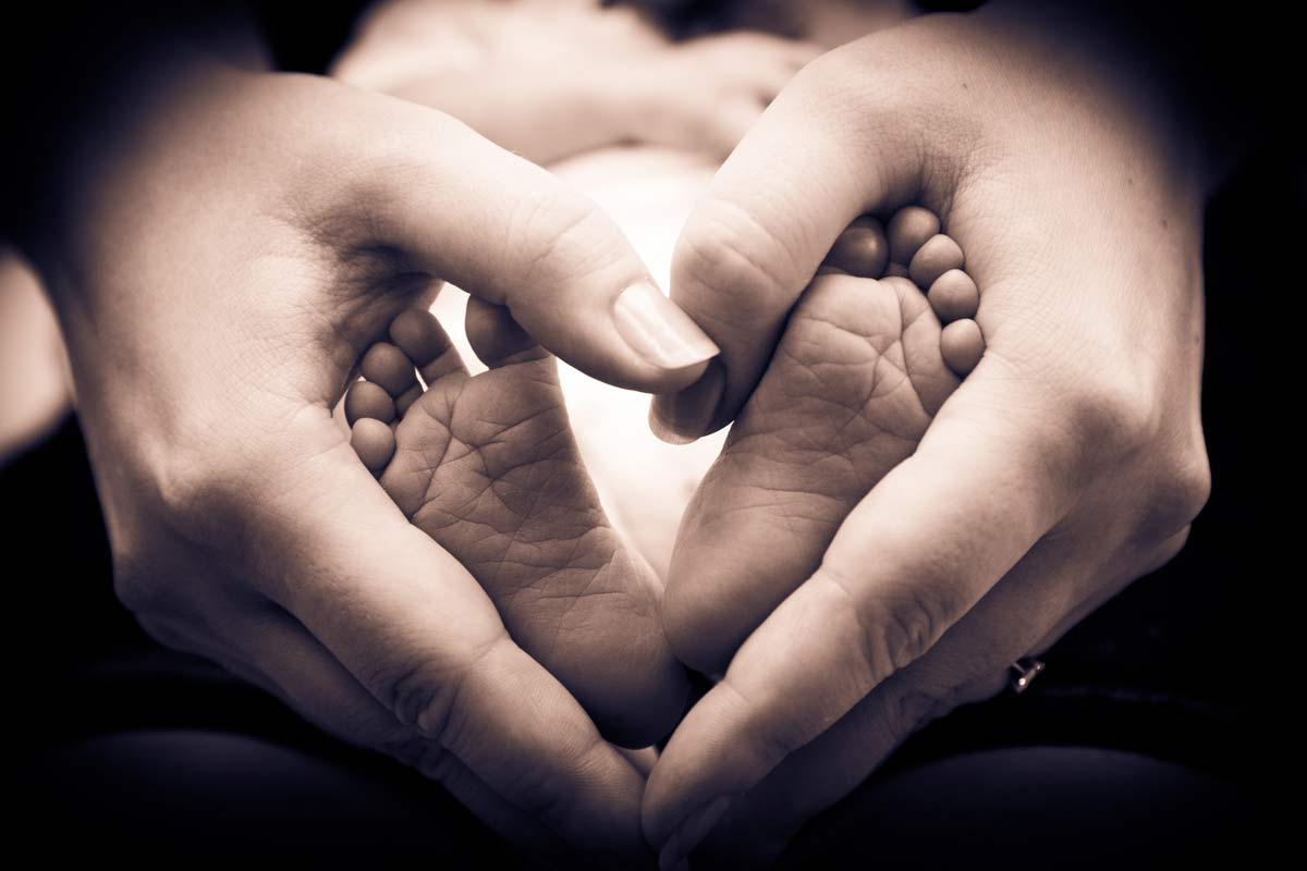Hands making a heart shape using babies feet.