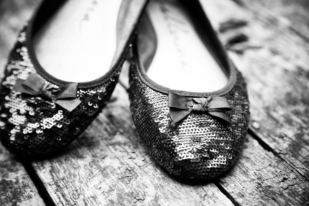 The brides blue sparkly wedding shoes placed on a barrel.