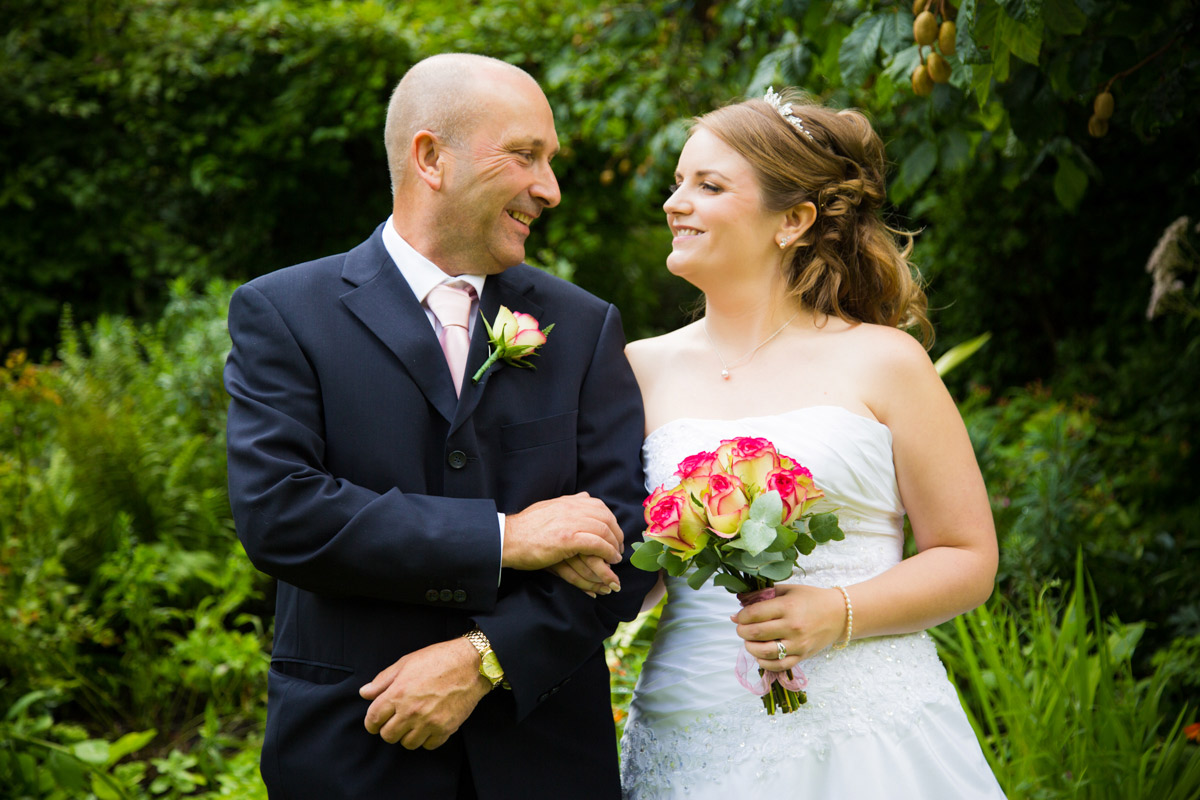 The bride and her father smiling at each other.