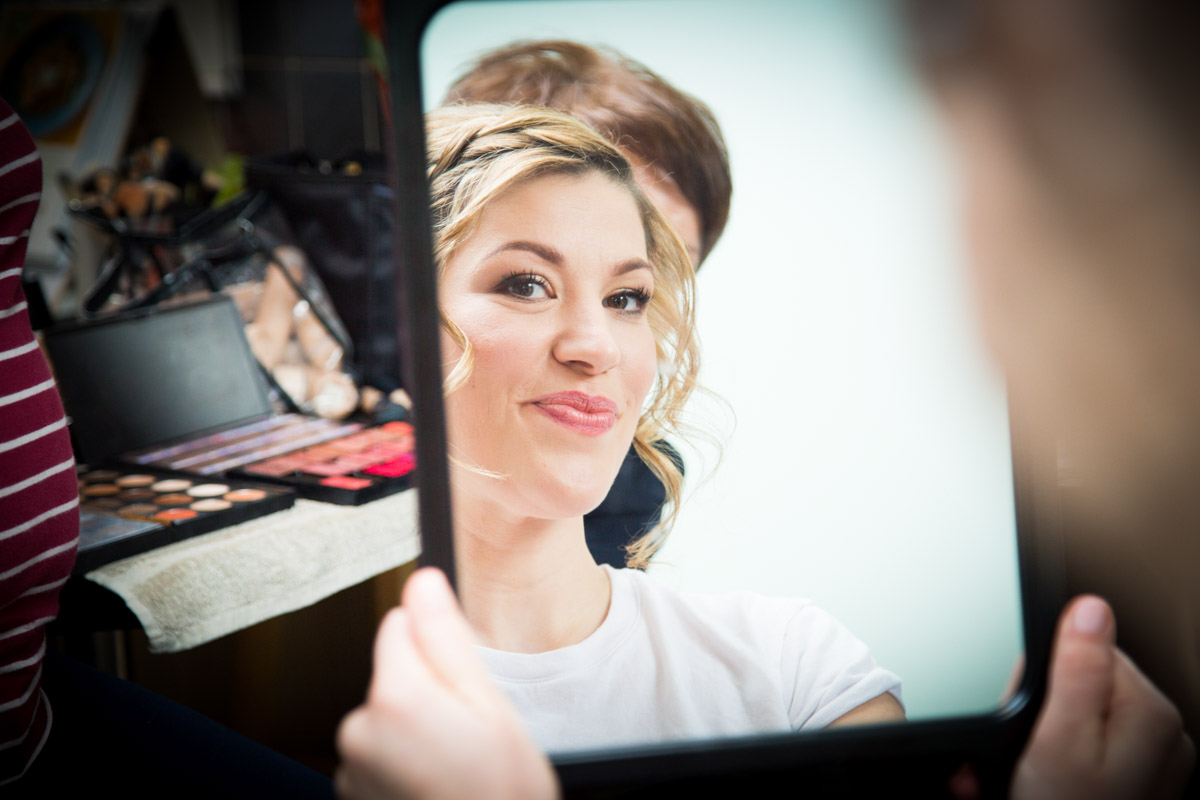 The reflection of the bride as she sees her wedding makeup.