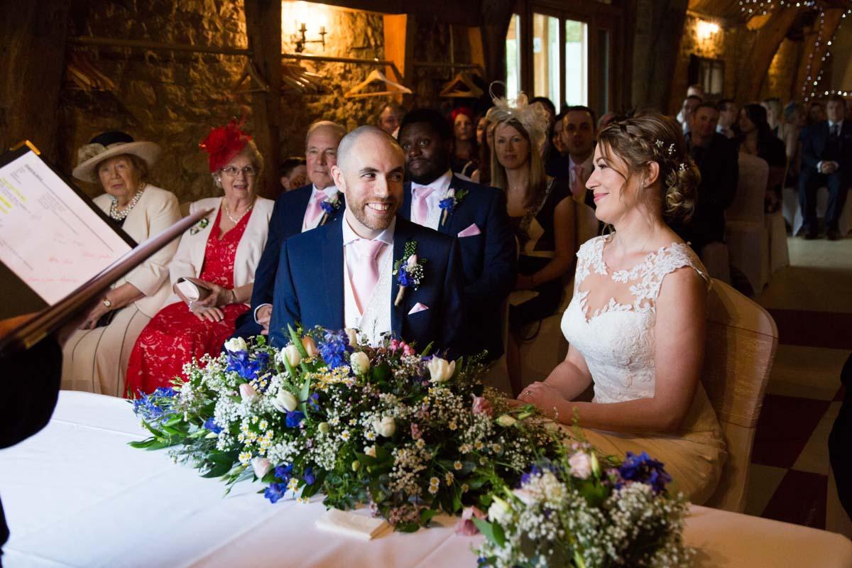 Bride and groom sat smiling in the wedding service in Aylesbury.