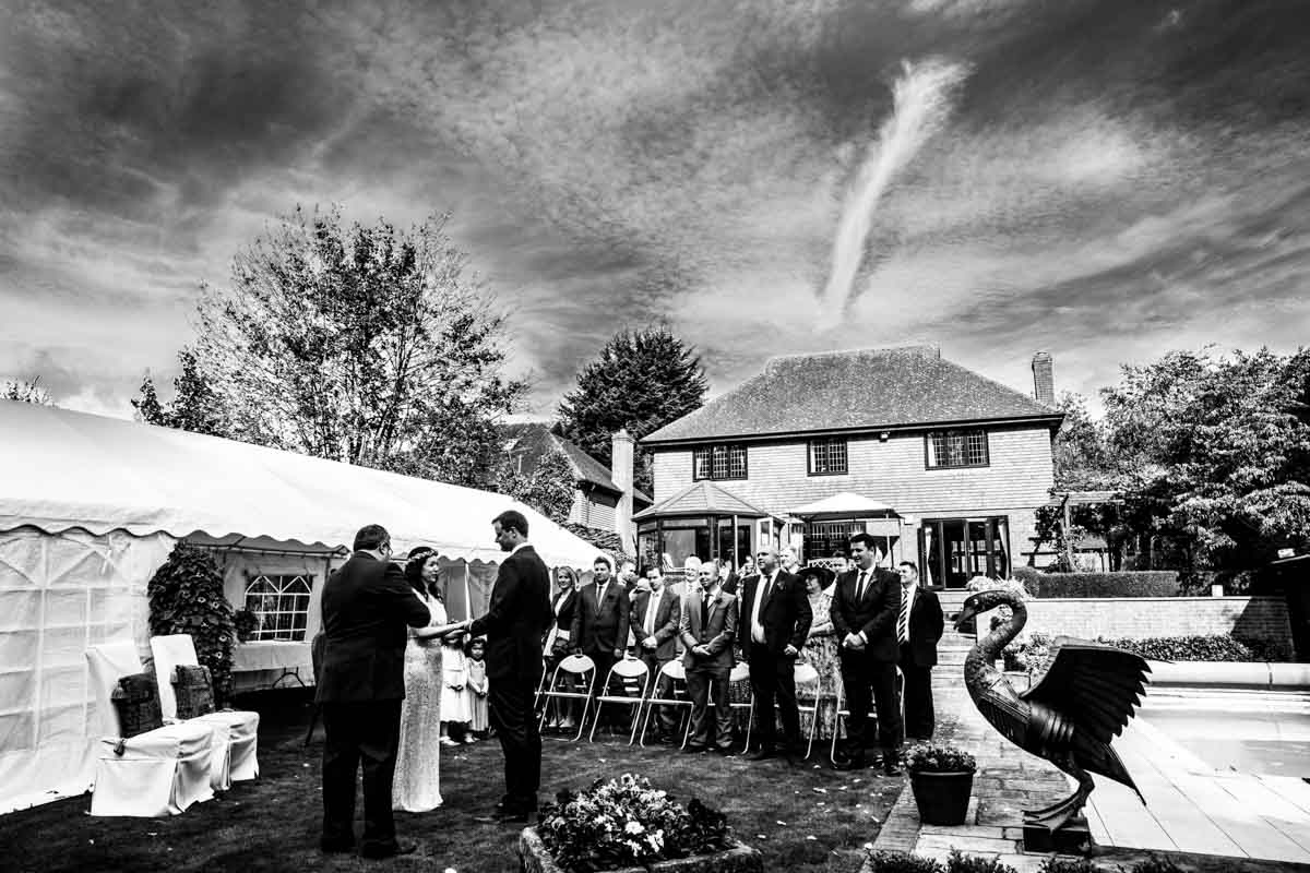 A Hereford wedding in a garden. The bride and groom and guests are standing during the service.