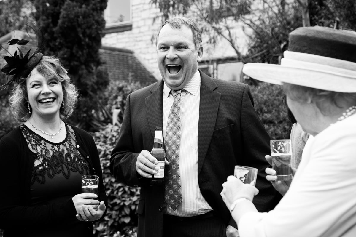 A wedding guest laughing in the venue garden.