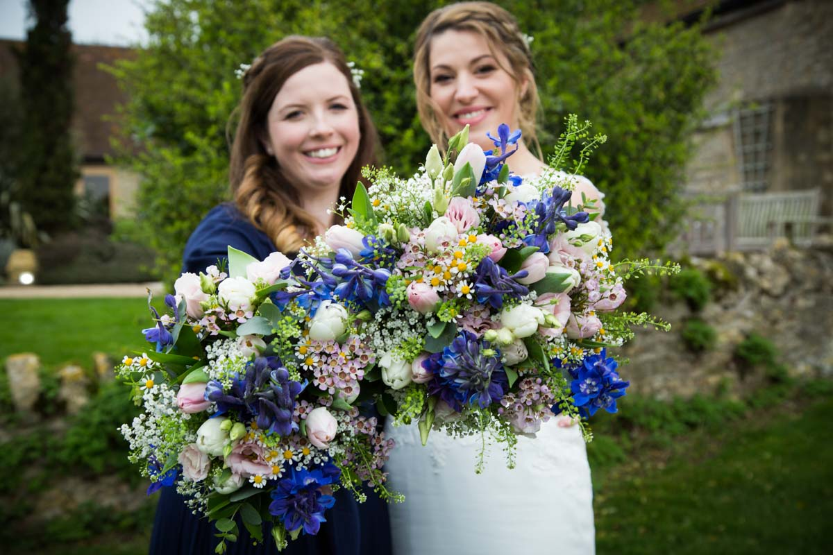Bride and bridesmaid holding up their wedding flowers. Blue wedding bouquet.