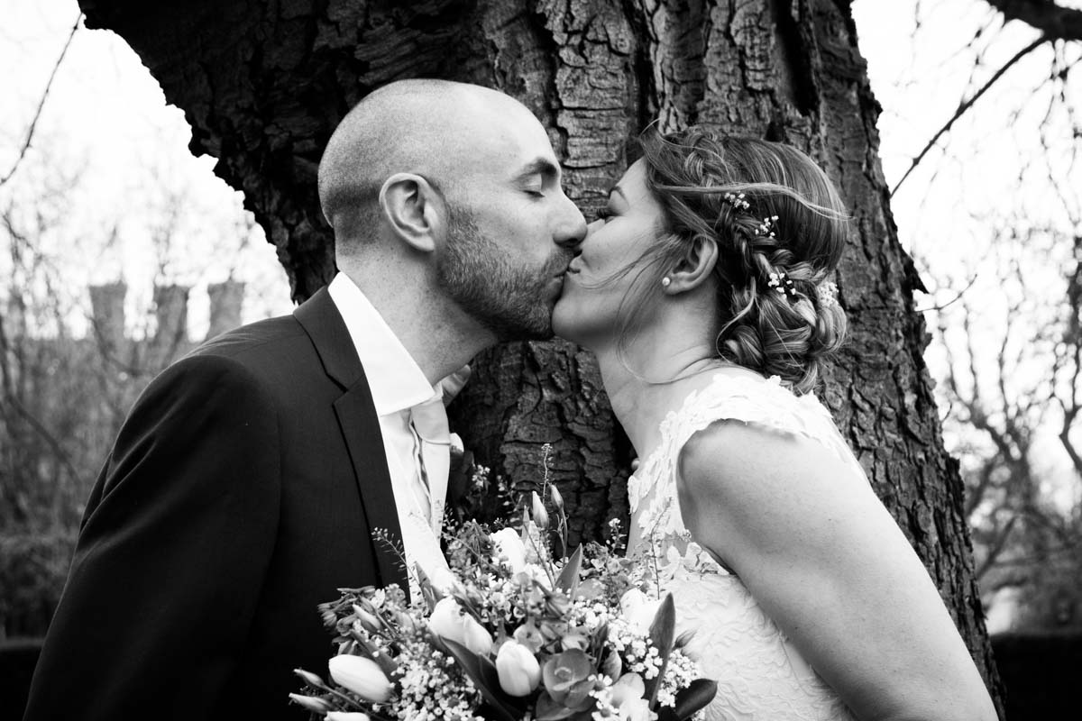 Bride and groom kissing in front of a tree
