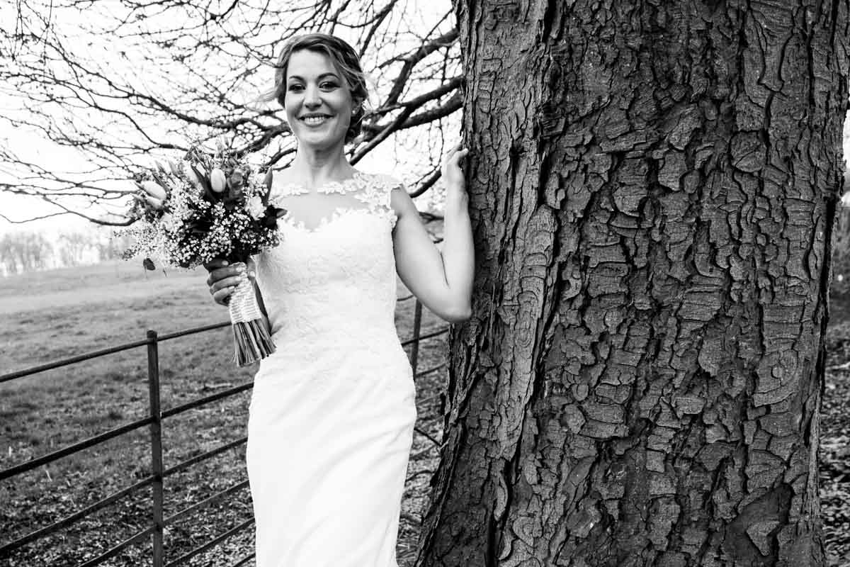 Bride holding her bouquet and leaning on a tree