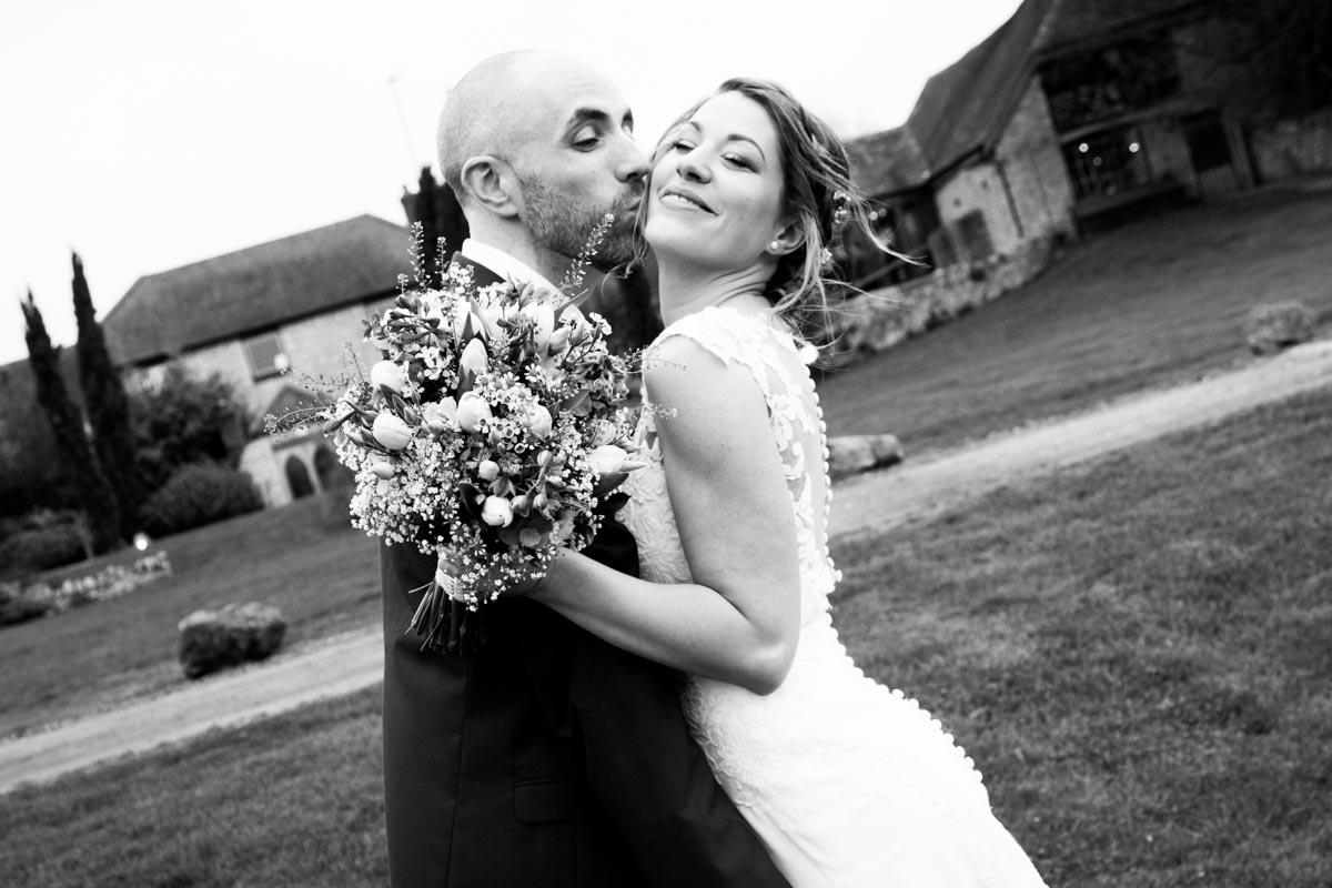 Glasgow wedding photographer. Groom holding the bride and kissing her on the cheek. Lochgoilhead wedding.