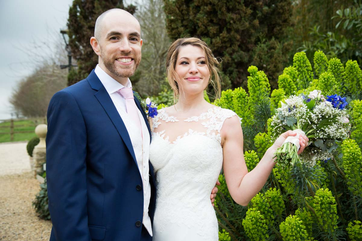 Groom with his arm around the bride in the Tythe Barn garden.