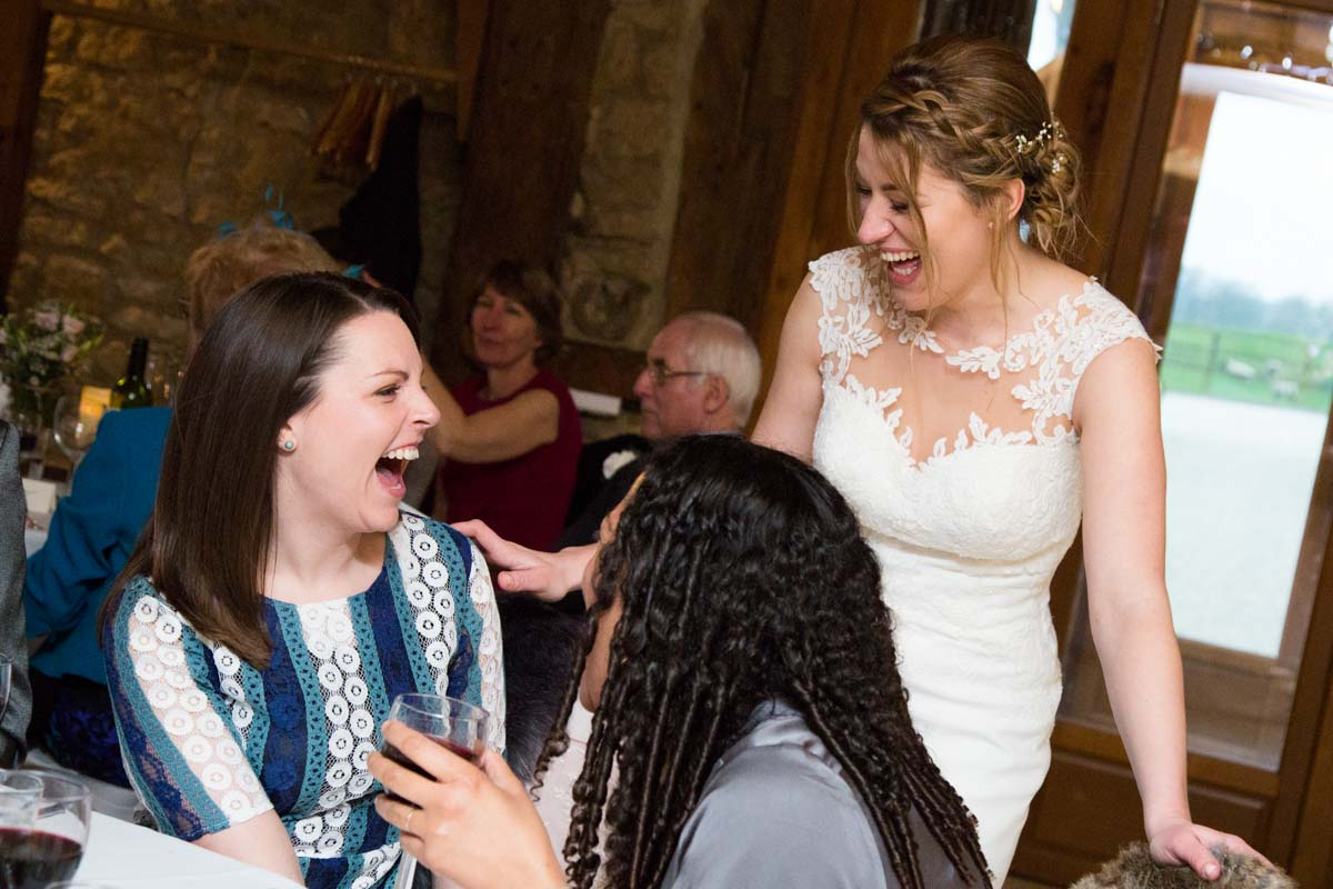 The bride laughing with guests during the wedding breakfast.