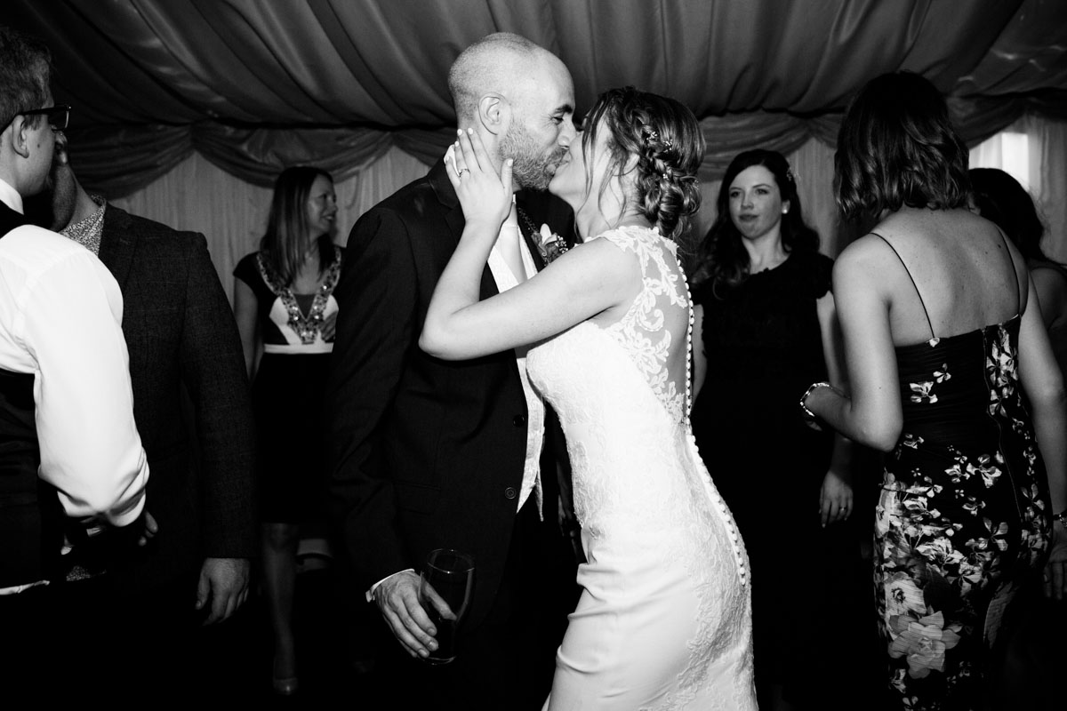 The bride holding her husbands face as she kisses him.