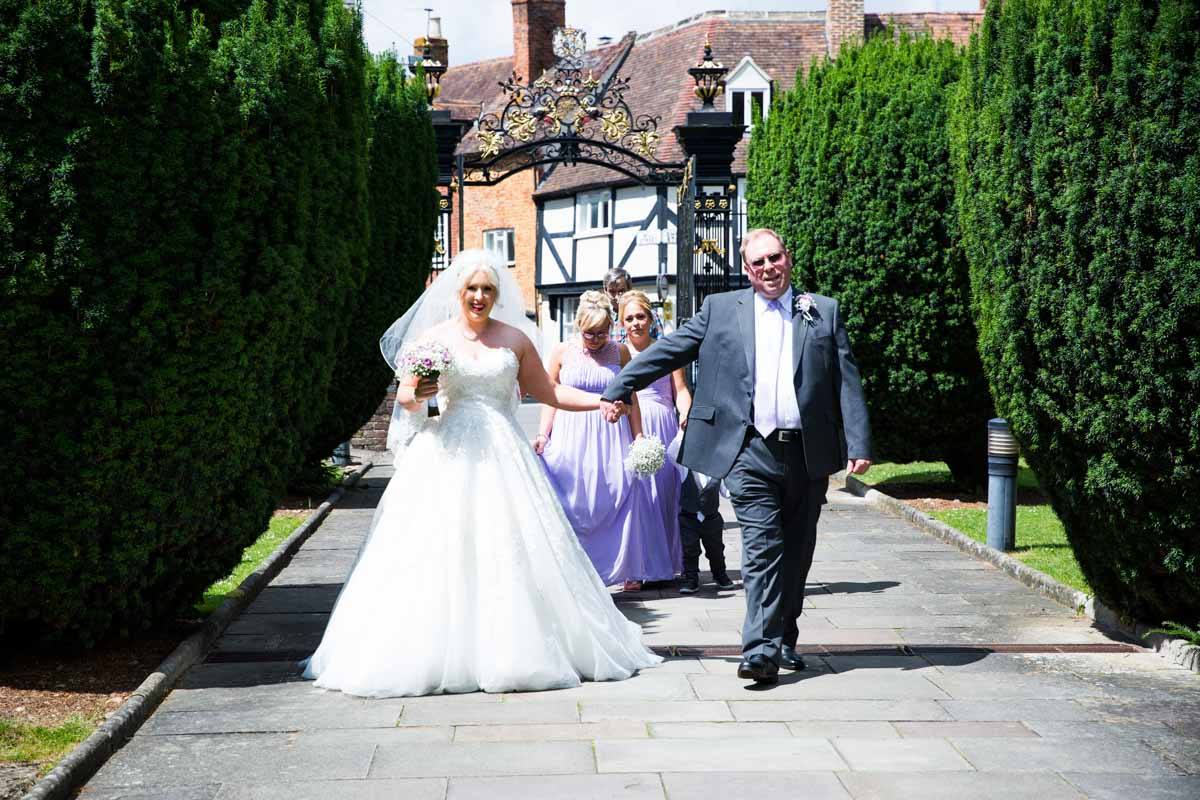 The bride and her father walking towards the Tewkesbury Abbey for her wedding service.