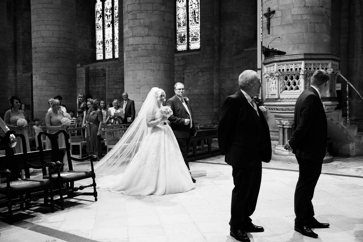 Bride being walked down aisle by her father at the Tewkesbury Abbey