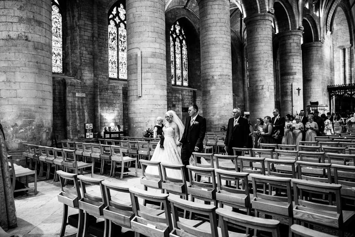 The bride and groom walking down the aisle of the Tewkesbury Abbey.