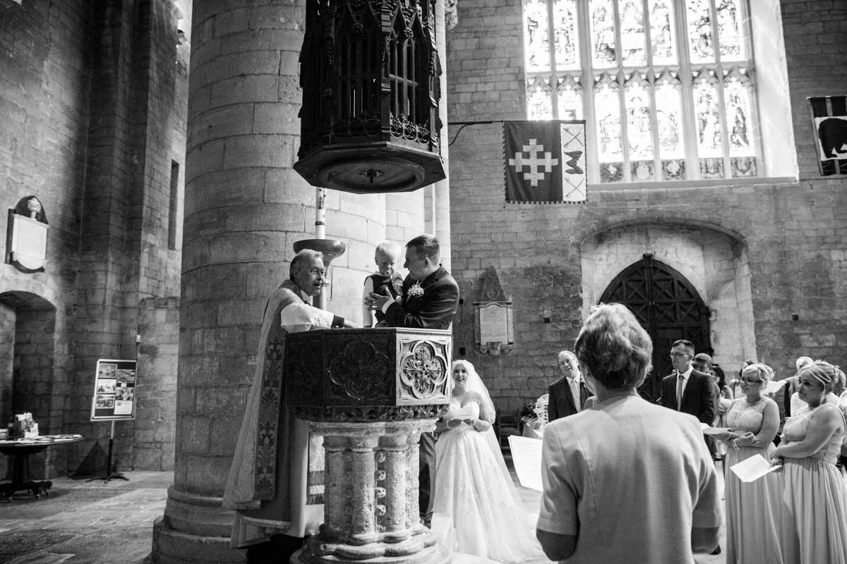 A little boy being Christened at the Tewkesbury Abbey.