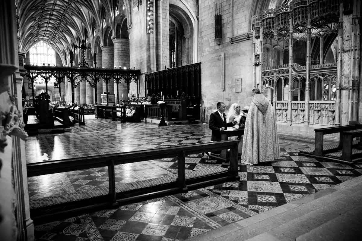 Bride and groom kneeling during their Tewkesbury Abbey wedding.