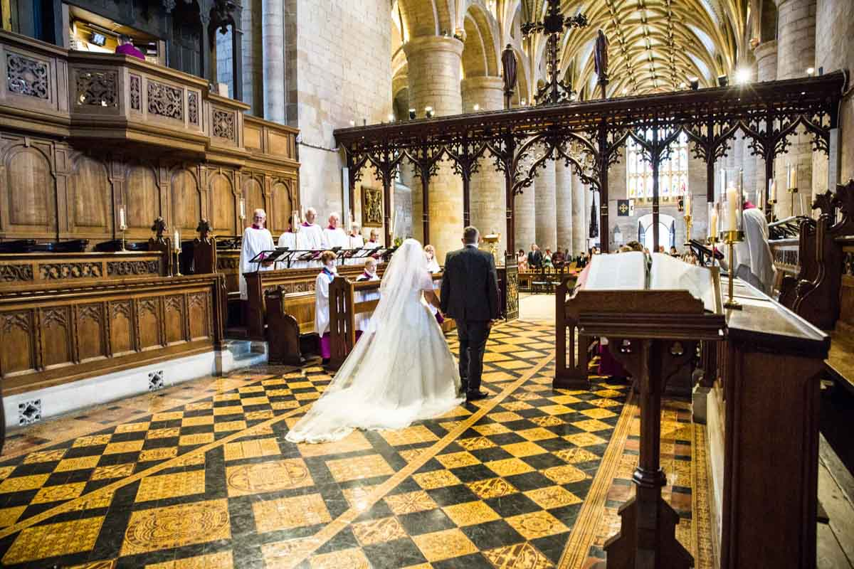 Bride and groom walking hand in hand in the Tewkesbury Abbey.