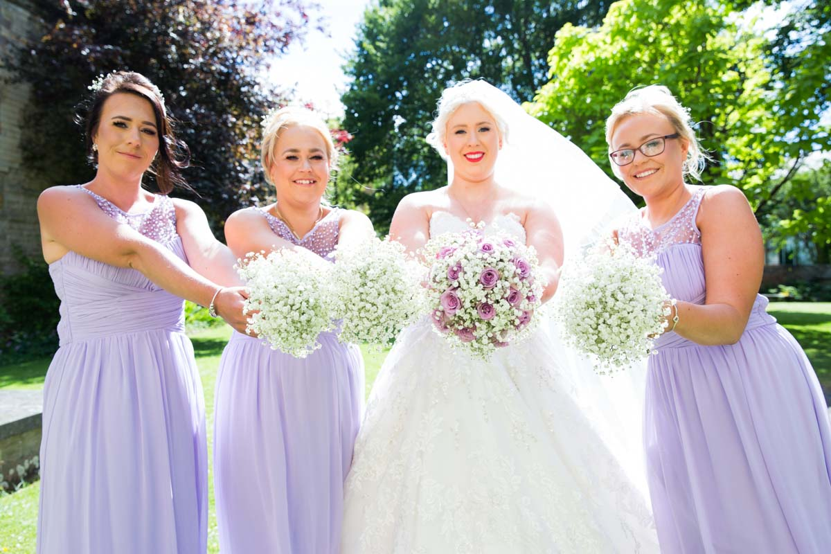 Bride and three lilac bridesmaids stood holding out their wedding bouquets.