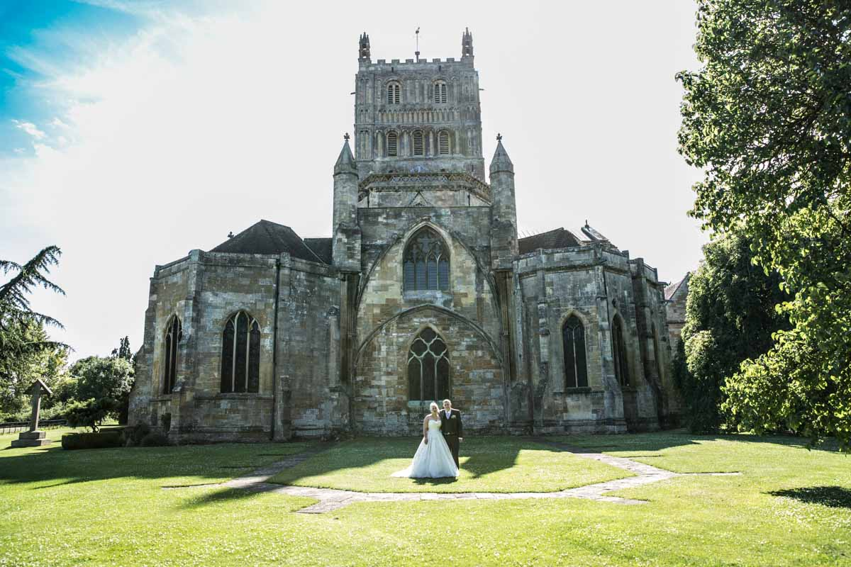 Bride and groom stood in front of the Tewkesbury Abbey.