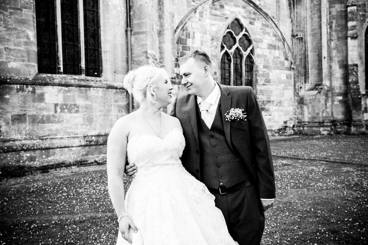 Bride and groom looking at each other lovingly after their Tewkesbury Abbey wedding.